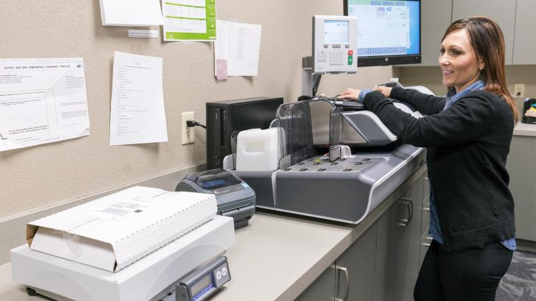 a smiling woman in a working in an office copy room
