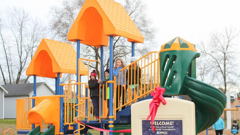 a group of happy elementary school children on new playground equipment purchased for a city park off of a Sourcewell awarded contract