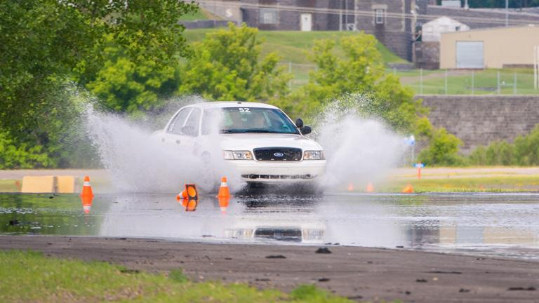 Officers in a test car initiate a practice of a controlled skid at the MHSRC