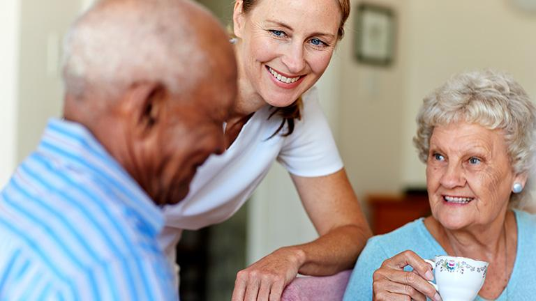 A care provider talking with senior citizens in an adult foster care home