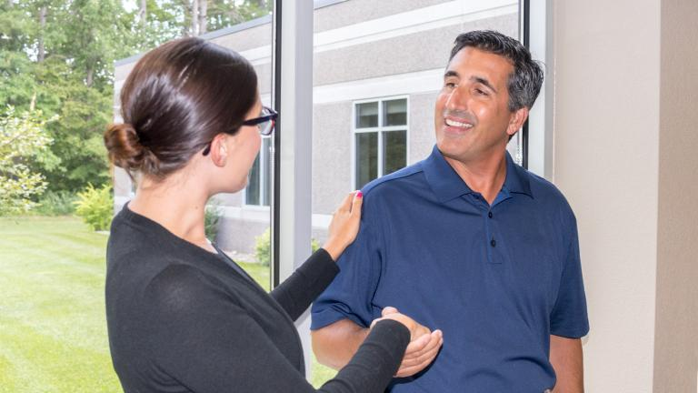 a member of Sourcewell's staff shaking hands and greeting a new employee at the front door