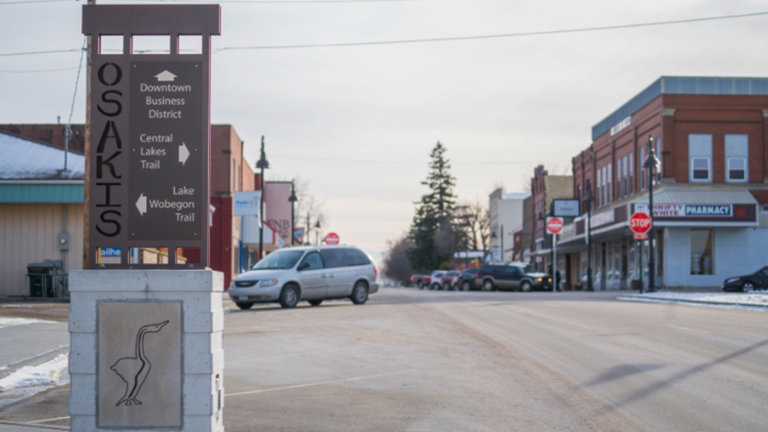Downtown intersection in Osakis, Minn. that features a corner sign that indicates downtown is ahead, the Central Lakes Trail is to the right, and the Lake Wobegon Trail is to the left.
