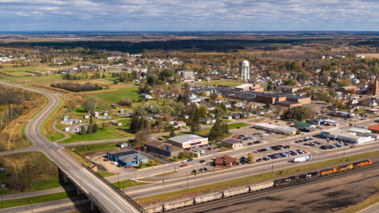 Aerial image of Staples, Minn. which includes the railway and highway in the foreground, and businesses, school, and water tower in the background