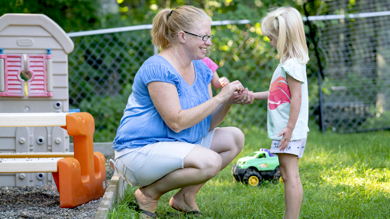 A licensed family child care provider crouches near a child while they play outdoors.