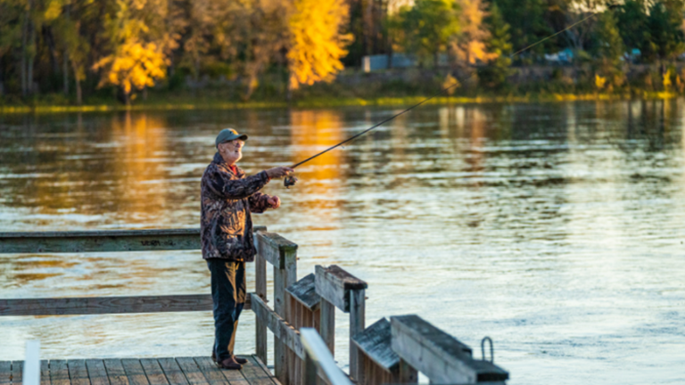 Image of a man fishing off of a park's dock at the Mississippi River in Brainerd, Minn.