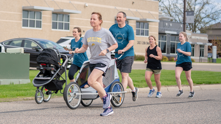 A group of government employees running a 5K as part of a wellness initiative available through Sourcewell's Insurance and Employee Benefits solutions.