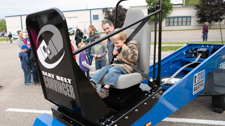 A young child experiences Toward Zero Death's popular Seat Belt Convincer, one of several pieces of specialized equipment purchased through Sourcewell funding that is available to local communities at minimal to no cost.