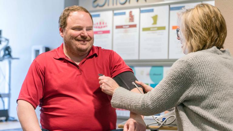 a Sourcewell employee getting a free blood pressure check, which is one of many available wellness initiatives and programs