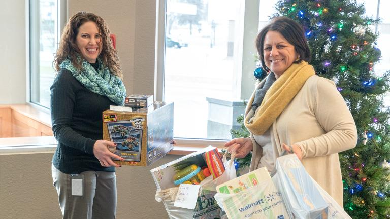members of the Sourcewell Human Resources team collects toys and holiday gifts donated by employees for a local charity benefiting children