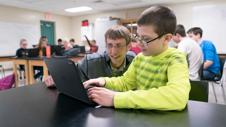 a teacher crouched at the desk of a student as they review a project on a laptop computer