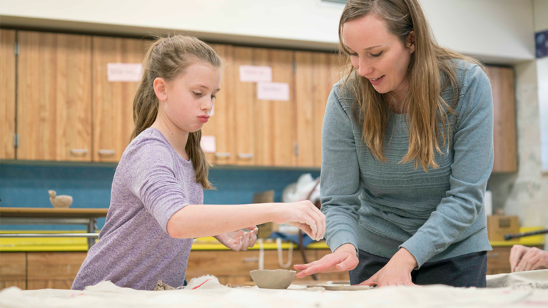 An art teacher guides her student on a pottery project after school recieves funding for a kiln through a Sourcewell funding program