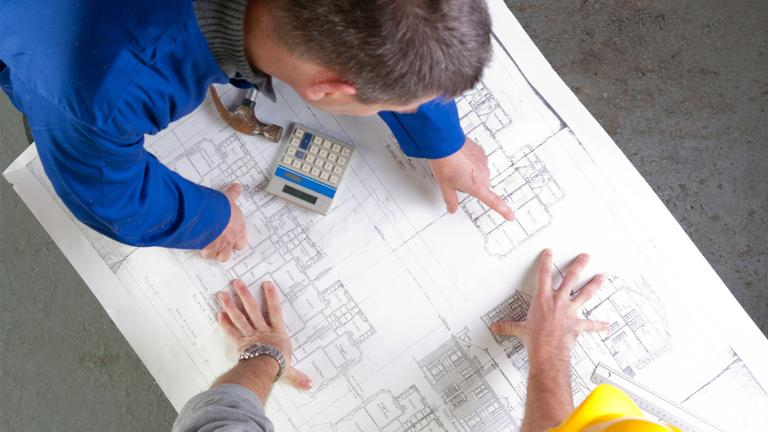 Two men leaning over a table reviewing a detailed building plan
