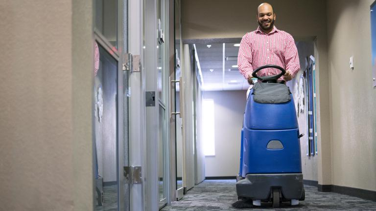 a smiling man on a ride on vaccuum cleaning the hall of an office building