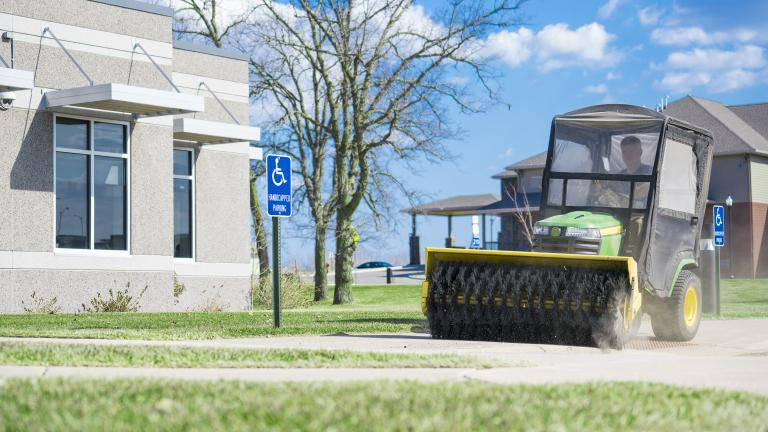 a riding mower with a sweeper attachment cleaning the sidewalk outside of an office building