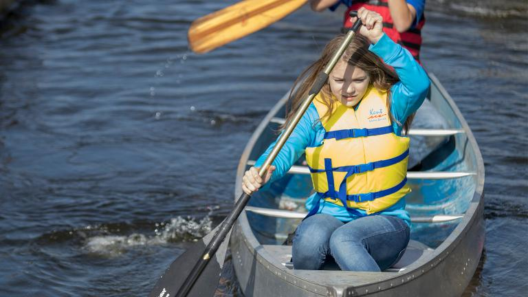 an preteen girl learning to canoe on one of the many rivers and lakes in Minnesota