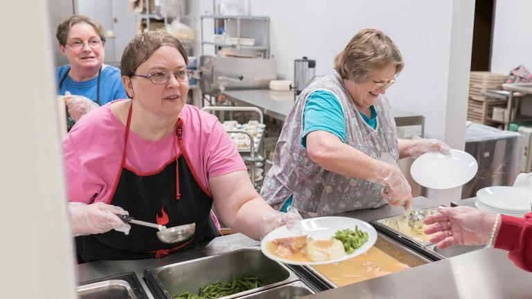 Volunteers at a local nonprofit food kitchen serve a warm meal