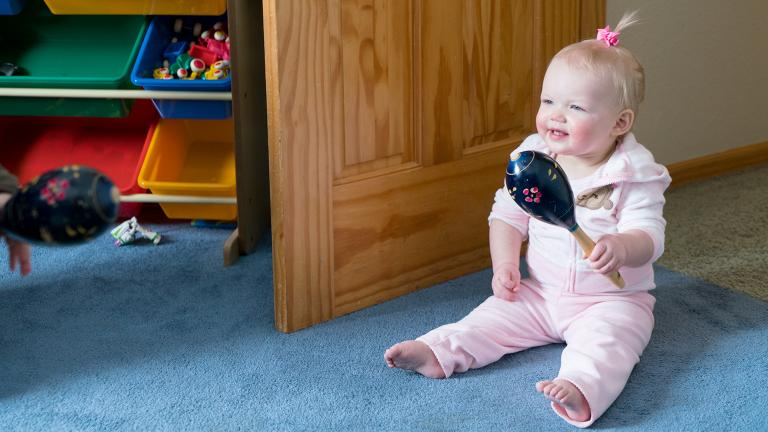 a baby sitting up and shaking a maraca toy as she learns at a licensed family child care