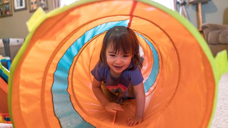 a happy young child crawling through a tent tunnel at a home-based child care