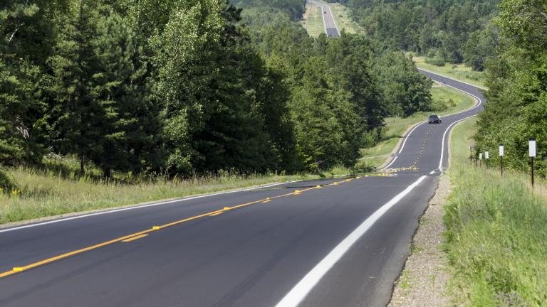 a newly paved asphalt road winding through a scenic wooded area