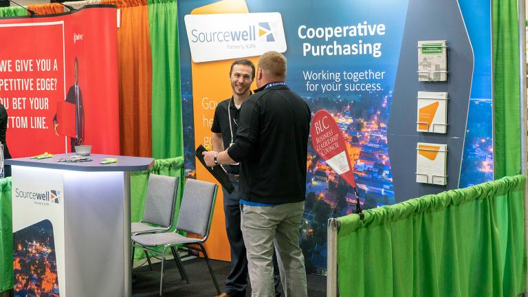 Sourcewell staff talking to a member in the Sourcewell booth at a industry tradeshow