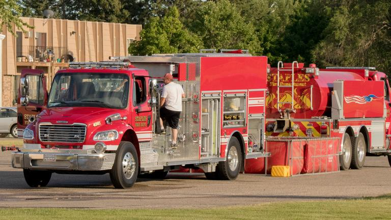 Two firetrucks purchased using a Sourcewell awarded contract being inspected by volunteer firefighters
