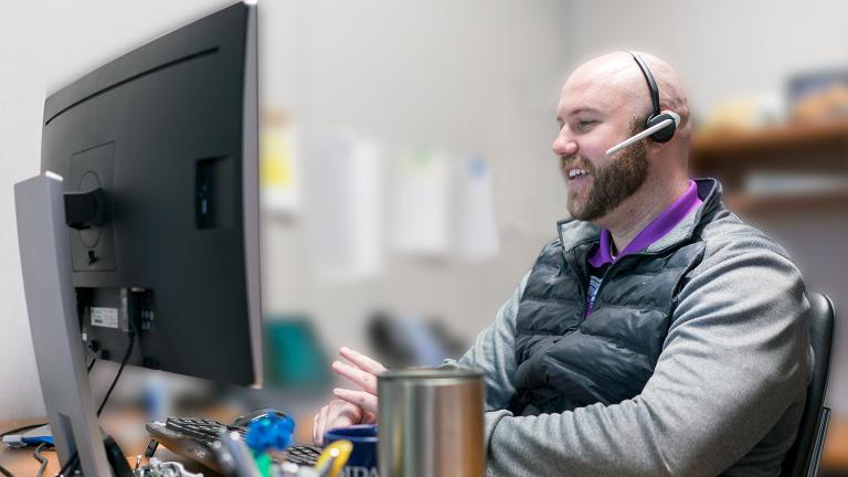man with a headset working at a computer in an office