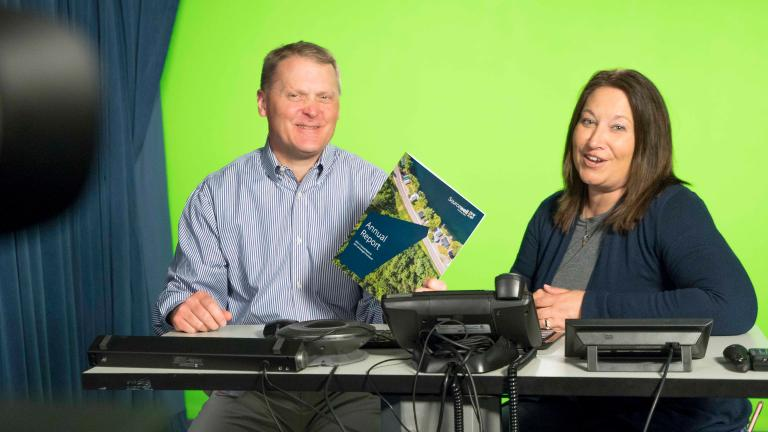Sourcewell staff in front of a green screen in a studio while presenting a webinar